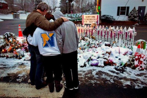 Members of the Rutter family of Sandy Hook, Conn., embrace early Christmas morning as they stand near memorials by the Sandy Hook firehouse in Newtown, Conn.,Tuesday, Dec. 25, 2012. People continue to visit memorials after gunman Adam Lanza walked into Sandy Hook Elementary School in Newtown, Conn., Dec. 14, and opened fire, killing 26, including 20 children, before killing himself.  (AP Photo/Craig Ruttle)