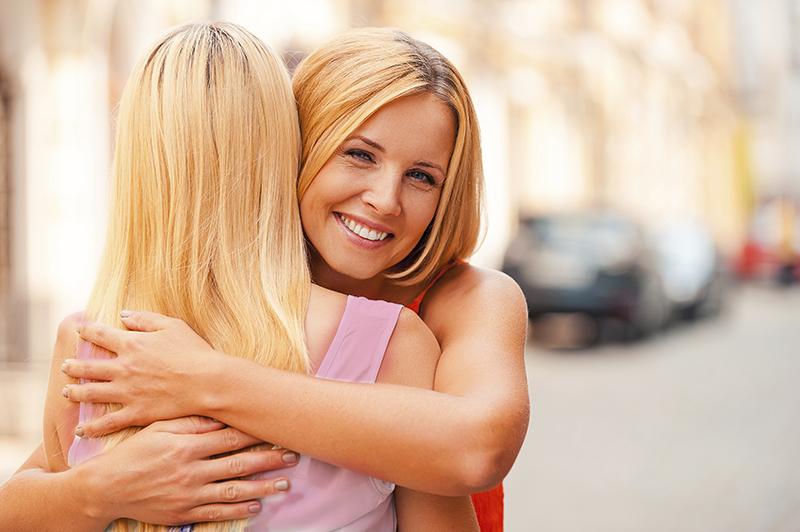 Two women hug during break in marriage education class.